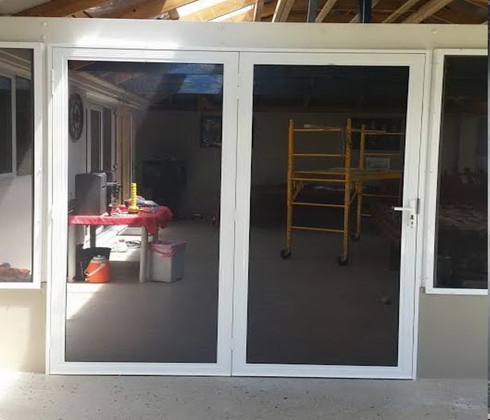 Construction Equipment Inside Room With White Framed Security Screen Door