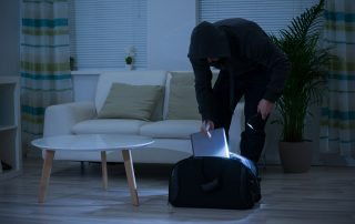 A Bugler In Living Room Holding Torch & Placing Laptop In Black Bag