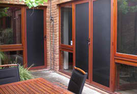 Patio Seating With Wooden Framed Screen Doors And Windows