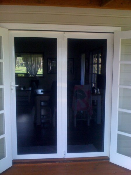 Dark Security Screen Mesh On White Framed Entrance Door