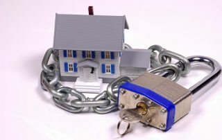 Miniature House Surrounded By Chain And A Lock With Key